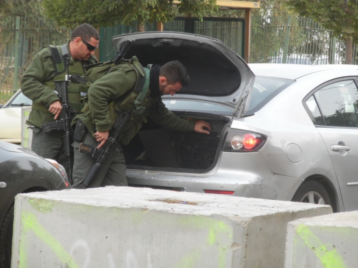 Border police inspecting a car at the checkpoint at the entrance to A-Tur in East Jerusalem. Photo taken by Esther Mack.